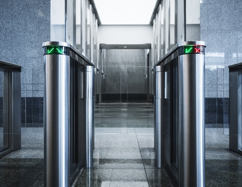 Silver security turnstiles in the lobby of an office building