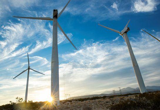 Sun setting on wind turbines on a wind farm