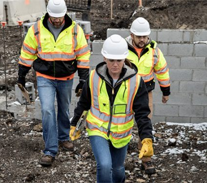 A Caucasian woman wearing a black hoodie, blue jeans, and safety vest is walking in front of a Caucasian man wearing brown pants and a safety jacket and a Caucasian man wearing a gray shirt on a work site.