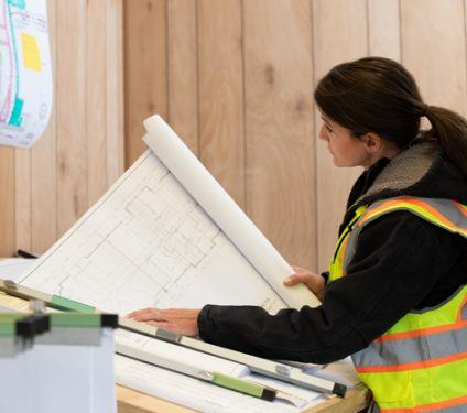 Female construction worker looking at sketch of building plans