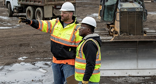 two workers on a construction site, one is pointing to something in the distance