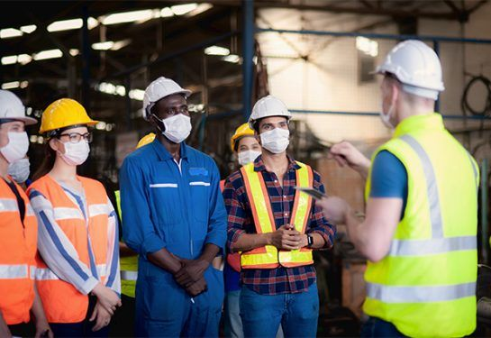A team of technicians, foreman and engineers accepting assignments from a manager in a meeting before work in which everyone wear surgical masks to prevent the coronavirus