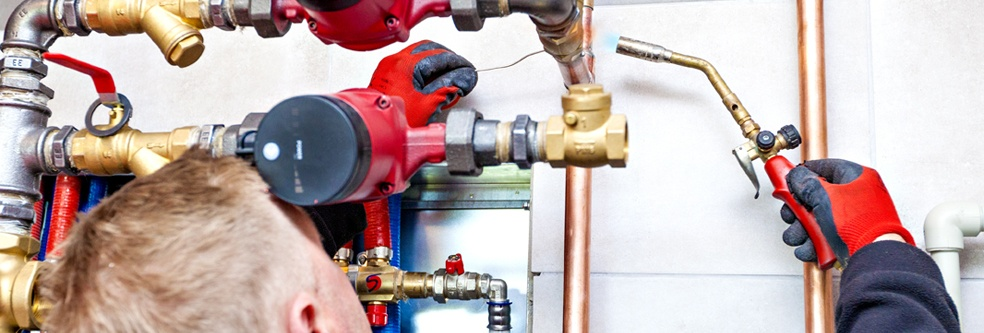 image of a plumber using a blowtorch on pipes