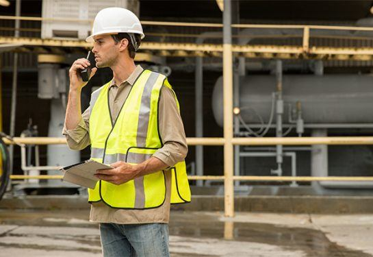 construction worker wearing a yellow safety vest and a white helmet on a walkie talkie
