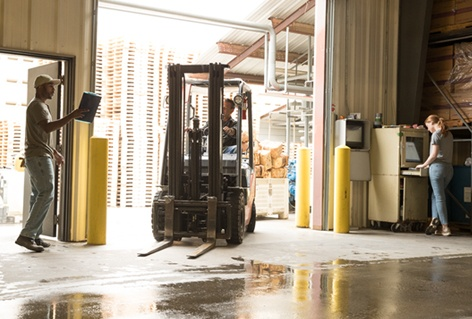 An employee holding a clipboard speaking with another employee who is driving a forklift in a warehouse