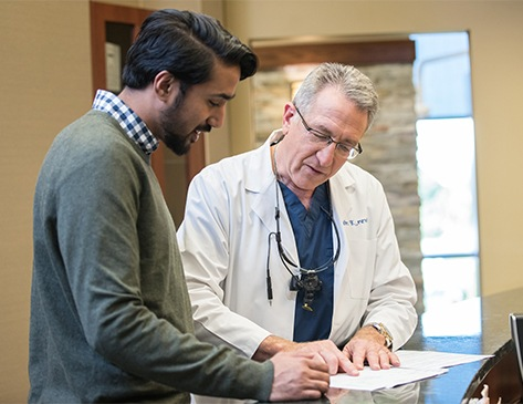 A Caucasian man wearing blue scrubs and a white lab coat standing in a doctors office talking to a Caucasian man wearing a plaid shirt and green sweater