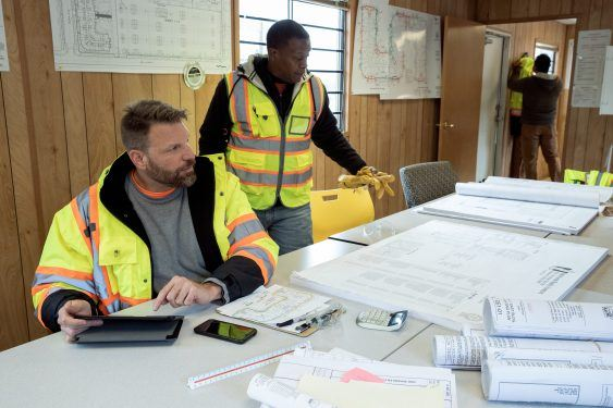 Construction workers sitting at a table with construction plans.