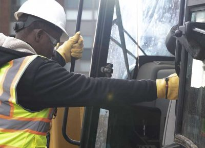Construction worker climbing into heavy machinery